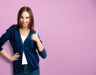 young woman showing thumbs up gesture, over purple
