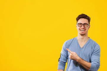 hipster man in glasses pointing happily away on orange yellow background