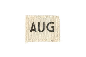 Closeup small picec of fabric calendar in august month isolated on white background