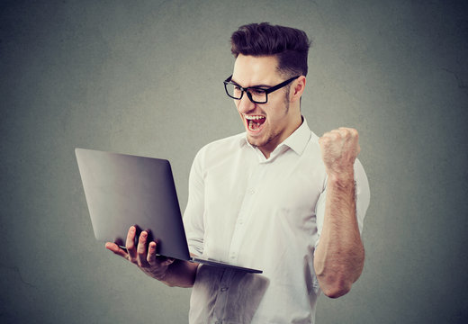 Excited man with laptop computer celebrating success