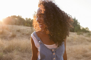 portrait outdoors of a beautiful young afro american woman smiling at sunset. Yellow background. Lifestyle