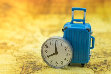 Time and Travel concept. Close up of miniature blue baggage with vintage round clock on world map.