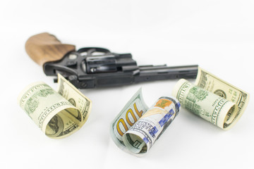 Pistol and money on a white background. The concept of crime is because of money.