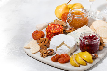 assortment of delicacy cheeses and snacks on board