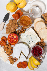 assortment of delicacy cheeses and snacks, vertical top view