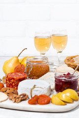 assortment of snacks - cheeses, nuts, fruits and wine, vertical