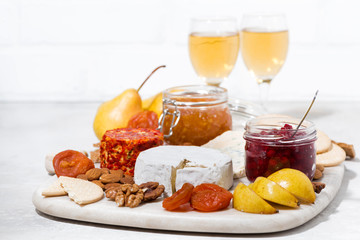 assortment of snacks - cheeses, nuts, fruits and wine