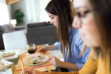 Two beautiful young women eating japanese food at home.