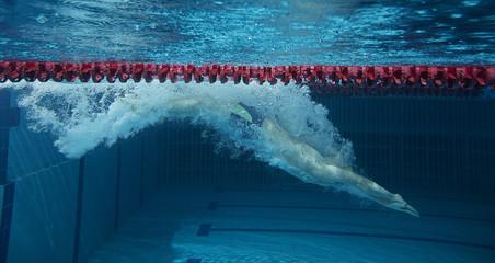 Man in in swimming pool. Underwater