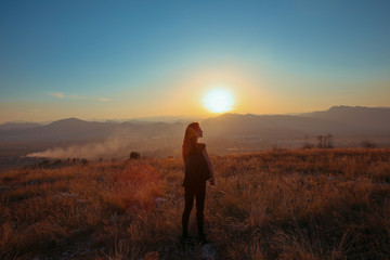 Sunset mountain. Tourist Free happy  woman outstretched arms with backpack enjoying life in wheat field. Hiker cheering elated and blissful with arms raised.