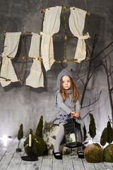 A beautiful three-year-old girl in a gray suit near a hemp with antique decorations.