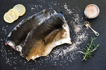 Close-up photo of fresh raw fish fillet with sea salt and lemon on black concreted table background