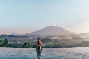 In de dag Lichtblauw beautiful girl staying near swimming pool with fantastic volcano Agung view