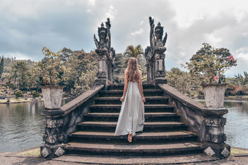 beautiful girl with long dark hair in elegant grey dress posing on old bridge in Tirta Gangga