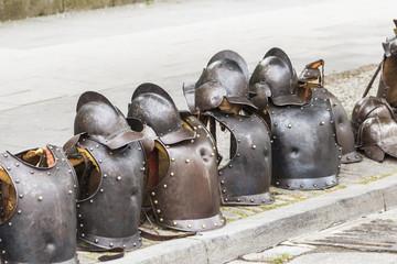 Leere Ritterrüstungen und Helme am Straßenrand.