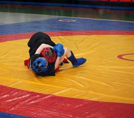Two boys are fighting on the wrestling mat