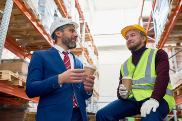 Waist up portrait of two warehouse workers taking break sitting on pellets drinking coffee and chatting