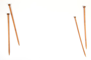 Wooden knitting needles on white background as frame