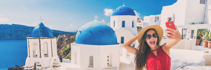 Wall Mural - Happy tourist taking selfie having fun on Europe summer vacation in Santorini, cruise destination panoramic banner. Asian woman funny holding mobile taking picture.