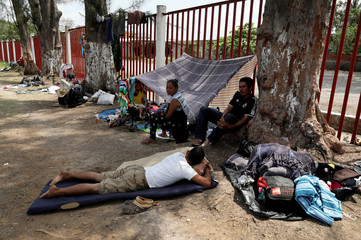 Central American migrants take a break from traveling in their caravan, as they journey to the U.S., in Matias Romero