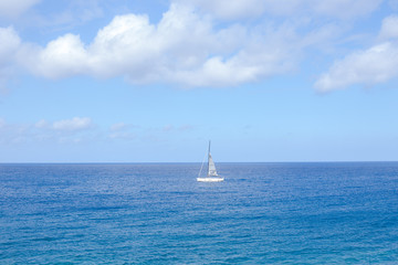 blue sky background with white big fluffy clouds and a boat in the sea