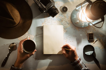 Adventure planning near gas lamp flat lay. Atmospheric old gear on map. Traveler, explorer hands in frame writing on empty notepad. Exploring, hiking empty space off grid poster, postcard, template.