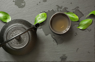 Green japanese tea on black slate background. Black teapot and bowl with green tea. Top view, copy space.