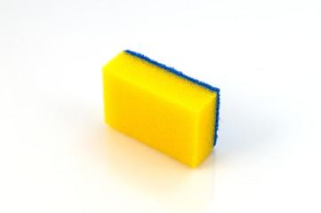 Поролоновая губка желтого цвета с синим слоем полимерного абразива для чистки посуды и бытовых поверхностей.