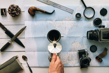 Adventure planning flat lay. Travel vintage gear on map. Man hand in frame pouring coffee from percolator into cup. Exploring lifestyle empty space poster, postcard concept