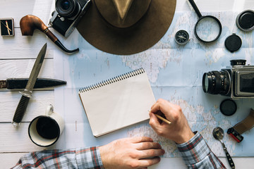 Adventure planning flat lay. Travel vintage gear on map. Man hands in frame writing on notepad. Exploring, hiking empty space poster, postcard, template.