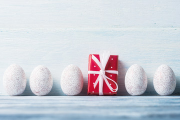 White Easter eggs and gift box over light wooden background.