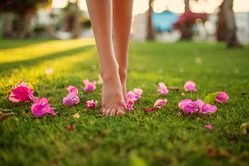 Close up female crossed legs walking on the grass,pink flowers on the grass