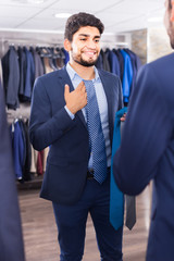 Customer male is picking up tie for jacket in front of the mirror