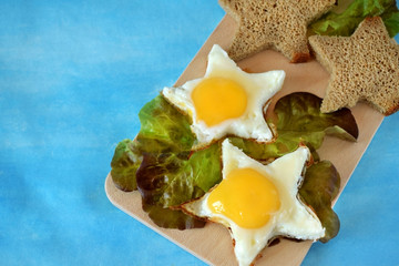 Fried eggs and slices of brown bread shaped as stars on a wooden board on blue background