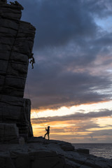 Silhouette of man climbing at sunset in Sardinia, Italy