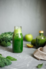 Healthy green smoothie with ingredients on gray background. Copy space