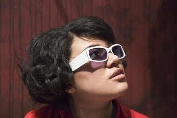 A young woman wearing white sunglasses.