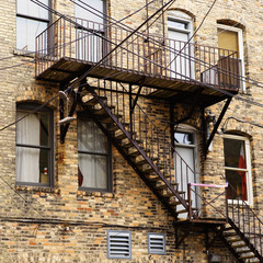 Metal stairs on the back of a old brick building.
