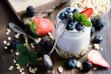 Yogurt and granola with berries, healthy cereal breakfast, toned image, selective focus
