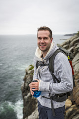 Portrait of hiker standing on cliff in Acadia National Park, Maine, USA