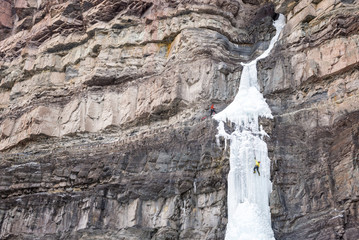 Man and woman ice climbing up frozen Cascade Falls waterfall, Ouray, Colorado, USA