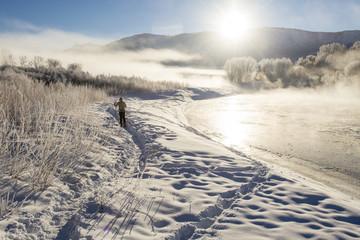 Woman cross country skiing on frosty morning along the Animas River, Durango, Colorado, USA