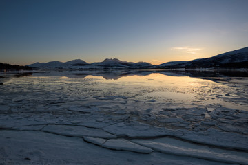 A Norwegian fjord near Tromsø covered with ice at sunset, Tromsø, Norway