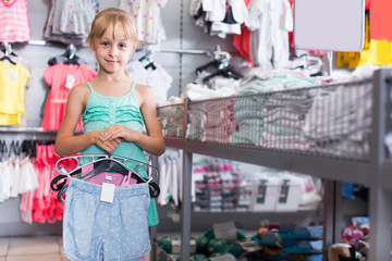 Portrait of girl choosing colored dress and wear in the shop