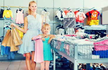 Female with packs and girl buying clothes in the dress shop