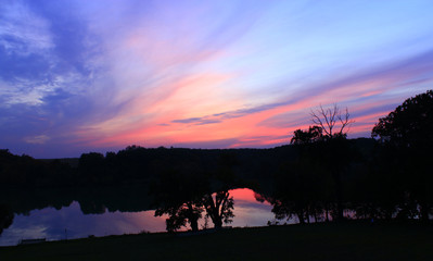 Dark sunset with crimson clouds. Twilight over lake. Dusk above river