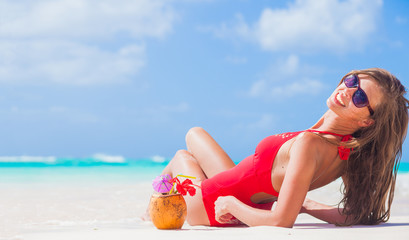 young longhaired girl in red swimsuit and wirh coconut tanning at tropical beach