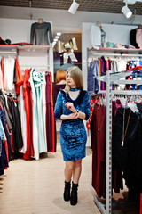 Blonde girl in blue dress in the clothing store boutique.