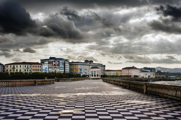 Clouds dressed in dark storms above the city of Livorno, with a view of the pitoresque Mascagni terrace, with the exclusive checkered floor floor and the unmistakable bandstand.