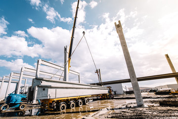 Details and tools on construction site with crane lifting prefabricated concrete framework, unloading and cargo details